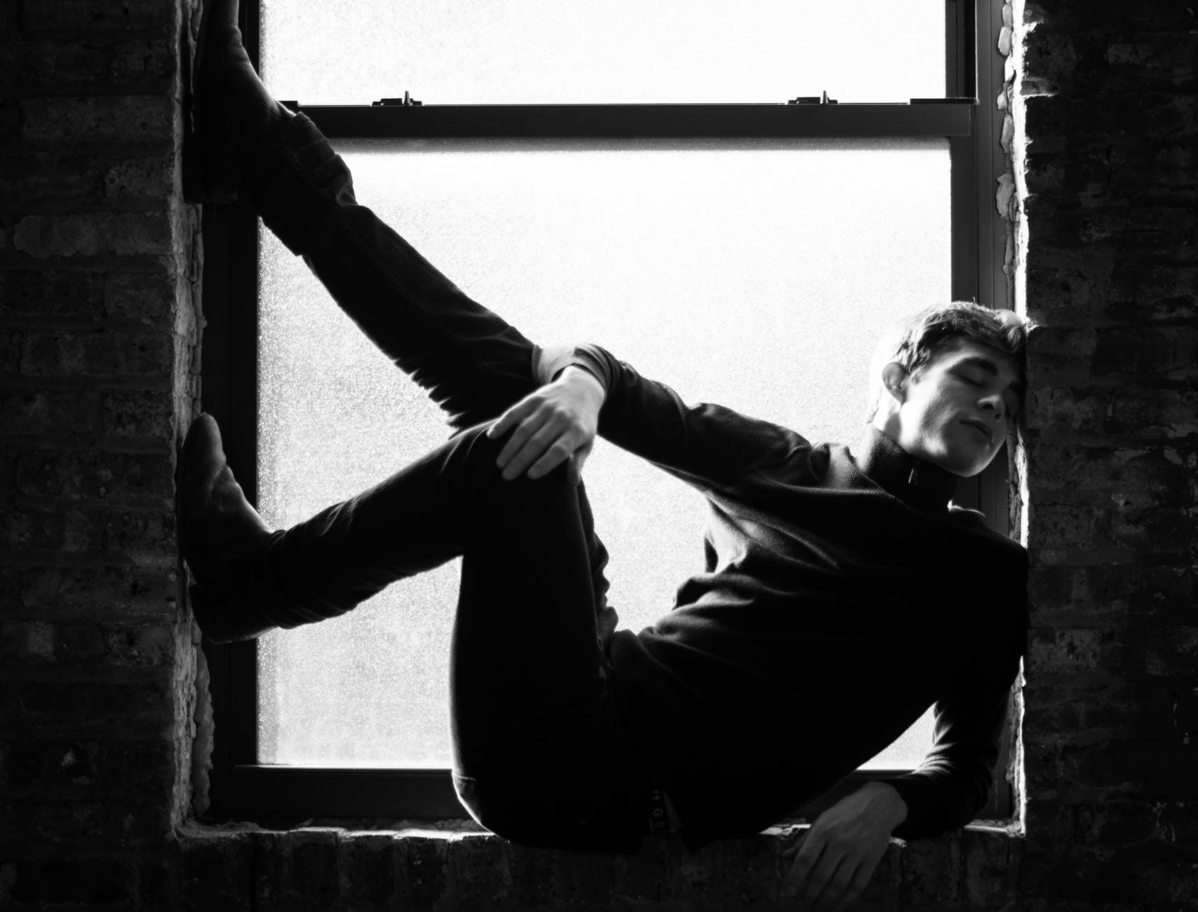grayscale photography of man sitting near window